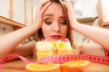 Woman with tape measure and cake. Diet dilemma. Royalty Free Stock Photo