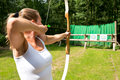 Woman target shooting a female archer aiming at a on a sunny day Royalty Free Stock Photos