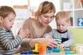 Woman teaches kids handcraft at kindergarten or playschool Royalty Free Stock Photo