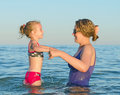 Woman teaching child to swim in the sea Royalty Free Stock Photos