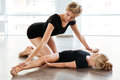 Woman teaching and stretching little girl ballerina in ballet class Royalty Free Stock Photo