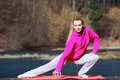 Woman teenage girl doing exercise on pier full length of young in pink tracksuit morning mat outdoor healthy active lifestyle Stock Image