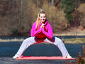 Woman teenage girl in tracksuit doing exercise on pier outdoor full length of young pink morning mat healthy active lifestyle Royalty Free Stock Images