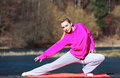 Woman teenage girl in tracksuit doing exercise on pier outdoor full length of young pink morning mat healthy active lifestyle Stock Image