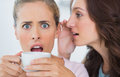 Woman telling secret to her friend and astonishing her while drinking coffee Stock Photos