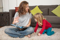 Woman telling a story to child sitting on carpet Royalty Free Stock Photo