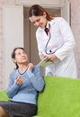 Woman tells the doctor the symptoms of malaise sick mature women focus on patient Stock Photography