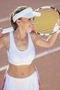 Woman with tennis racquet smiling standing on court vertical image Stock Images