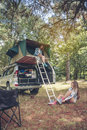 Woman in tent over car and other putting hiking boots Royalty Free Stock Photo