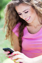 Woman text messaging attractive with mobile phone smiling Stock Photography