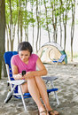 Woman text messaging on cell phone at campsite Stock Image