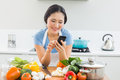 Woman text messaging in front of vegetables in kitchen smiling young the at home Stock Photos