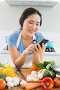 Woman text messaging in front of vegetables in kitchen smiling young the at home Royalty Free Stock Photos