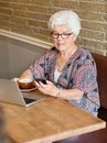 Woman text messaging through smartphone in cafe senior with laptop and coffee cup Royalty Free Stock Image