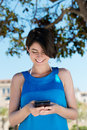 Woman texting on her mobile phone low angle view of an attractive young under the shade of a tree Stock Photography