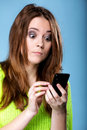 Woman texting while looking surprised on phone has reaction of surprise as she reads a message her mobile blue background Stock Photography