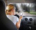 Woman texting on phone and driving car a young is the cell with a road in the windshield for an danger or distracted concept Stock Photo