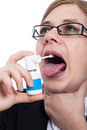 Woman with throat pain using oral spray Royalty Free Stock Photo