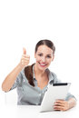 Woman with thumb up and digital tablet smiling Royalty Free Stock Image