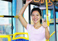 Woman thump up by bus Stock Photo