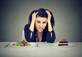 Woman tired of diet restrictions deciding to eat healthy food or cake she is craving Royalty Free Stock Photo