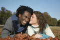 Woman about to kiss man in field romantic young women men while lying Royalty Free Stock Photography