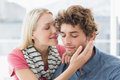 Woman about to kiss man on his cheek happy casual young women men Royalty Free Stock Images