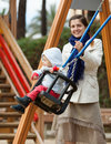 Woman with toddler on swings happy women in autumn Royalty Free Stock Photo