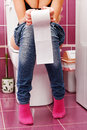 Woman in the toilet with a big hank of paper Stock Photos