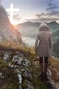 Woman on top of the mountain looking at the Christian Cross Royalty Free Stock Photo