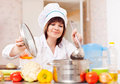 Woman in toque cooks with ladle kitchen Royalty Free Stock Image