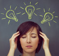 Woman touches her head on a background of light bulbs Royalty Free Stock Photo