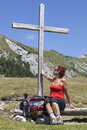 Woman touching wooden cross resting under on the mountain beautiful sunny summer day in the alps Royalty Free Stock Photo