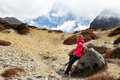 Woman tourist backpacker resting rock ama dablam mountain trail stone snow peak base camp trekking route nepal traveling tourism Royalty Free Stock Photography