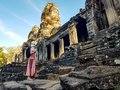 Woman tourist in Bayon temple in Angkor Wat