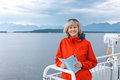 Woman tourist sailing on a sightseeing ferry boat happy smiling holding map norway fjord at background Stock Image