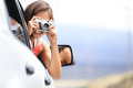 Woman tourist taking photo in car with camera driving on road trip travel vacation girl passenger picture out of window Stock Photography