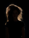 Woman with tousled hair in black shadow front view of n background Royalty Free Stock Photos