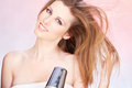 Woman with towel holding blow dryer Royalty Free Stock Photo