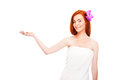 Woman in towel smiling holding somthing in hand over white background Stock Photos