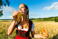Woman with tracht beer and pretzel in bavaria young bavarian drinking keeping a dirndl at meadow Royalty Free Stock Image