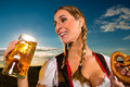 Woman with tracht beer and pretzel in bavaria young bavarian drinking keeping a dirndl at meadow Stock Photos