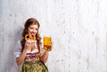 Woman in traditional bavarian dress holding beer and pretzel Royalty Free Stock Photo