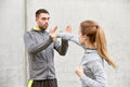 Woman with trainer working out self defense strike