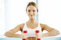 Woman training with dumbbells attractive young holding and smiling at camera Stock Photo