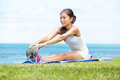 Woman training fitness stretching legs exercise outside by the ocean sea beautiful fit female girl model sitting on grass Royalty Free Stock Photo