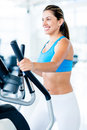 Woman training at the gym beautiful on an x trainer Royalty Free Stock Photos