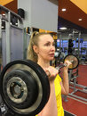 The woman trains in a gym with a bar Royalty Free Stock Photography