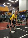 The woman trains in a gym with a bar Stock Image