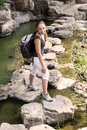 Woman travel jungle backpack caucasian female model cross river nature Royalty Free Stock Photo